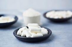 Créatine, Bêta-alanine, capsules de taurine et un scoop de protéine de lactalbumine images stock