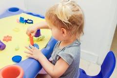Créativité d'enfants L'enfant sculpte de l'argile La petite fille mignonne d'enfant en bas âge moule de la pâte à modeler sur la  photo libre de droits