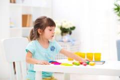 Créativité d'enfants L'enfant sculpte de l'argile La petite fille mignonne moule de la pâte à modeler sur la table dans la chambr image libre de droits