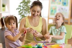 Créativité d'enfants Les enfants sculpte de l'argile Les petites filles mignonnes avec la mère moule la pâte à modeler sur la tab Photo libre de droits