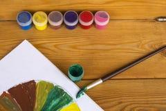 Créativité du ` s d'enfants Peintures de dessin 12 couleurs de peinture Palette de couleur Peintures sur un fond en bois watercol photo stock