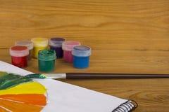 Créativité du ` s d'enfants Peintures de dessin 12 couleurs de peinture Palette de couleur Peintures sur un fond en bois watercol photographie stock libre de droits