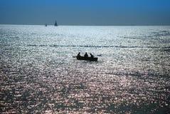 Crépuscule au-dessus de mer, pêcheurs Photos libres de droits