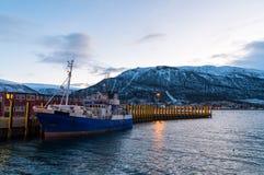 Crépuscule dans le pilier de Tromso avec le bateau de pêche garé Images libres de droits