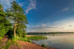 Crépuscule merveilleux au lac d'été avec les nuages dynamiques images libres de droits