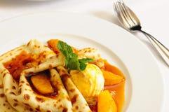 Crêpe con i arancio-pezzi ed il gelato immagini stock