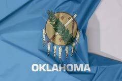 Crêpe de drapeau de tissu de l'Oklahoma et pli avec l'espace blanc, les états de l'Amérique photographie stock libre de droits