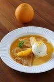 Crêpe dei pancake con il gelato e la salsa arancio Immagine Stock