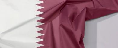 Crêpe et pli de drapeau de tissu du Qatar avec l'espace blanc images stock