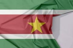 Crêpe et pli de drapeau de tissu du Surinam avec l'espace blanc illustration stock