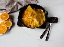 Crêpe francesi tradizionali Suzette con salsa arancio in padella del ghisa immagini stock libere da diritti