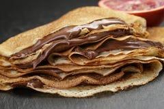 Crêpe o blinis con la crema e l'arancia del cioccolato Immagini Stock