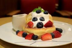 Crêpe pelucheuse de soufflé avec les baies fouettées fraîches de crème et de mélange du plat blanc avec le broc de sirop images libres de droits