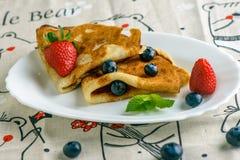 Crêpes avec des baies sur le petit déjeuner photo stock