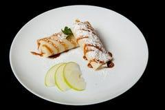 Crêpes avec des pommes sur un fond noir Le dîner de mariage avec de la viande de roulis a fumé et des tomates images stock