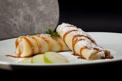Crêpes avec des pommes sur un fond noir Le dîner de mariage avec de la viande de roulis a fumé et des tomates photographie stock libre de droits