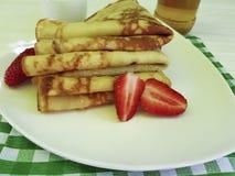 crêpes avec du miel de fraise faisant cuire le verre de tradition de lait sur en bois blanc images stock