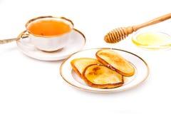 Crêpes avec du miel et le thé Photographie stock