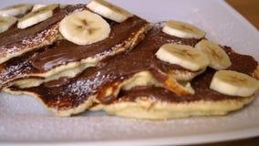 Crêpes avec la banane et le chocolat, petit déjeuner délicieux avec des crêpes banque de vidéos