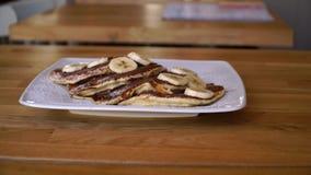 Crêpes avec la banane et le chocolat, petit déjeuner délicieux avec des crêpes clips vidéos