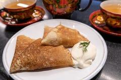 Crêpes avec la crème sure et le thé dans le plat traditionnel pour des vacances Maslenitsa images stock