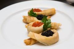 Crêpes avec le caviar d'un plat blanc Foyer sélectif shallow image libre de droits