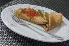 Crêpes avec le caviar rouge d'une plaque Photo stock