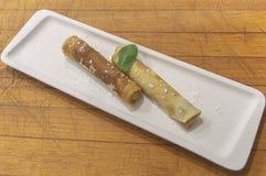 Crêpes avec le fromage blanc, d'un plat blanc, arrosé avec du sucre en poudre, décoré d'une feuille en bon état photographie stock