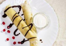 Crêpes avec le fromage blanc, les raisins secs et la crème sure sur un blanc photographie stock libre de droits