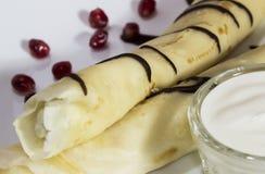 Crêpes avec le fromage blanc, les raisins secs et la crème sure sur un blanc photos libres de droits