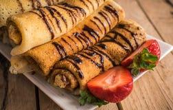 Crêpes avec le nutella et les fraises Fond en bois rustique Images stock