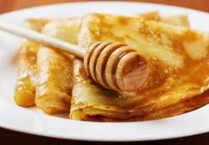 Crêpes avec le sirop de miel d'un plat blanc Image stock