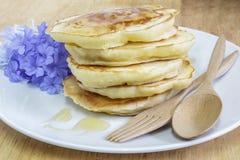 Crêpes avec le sirop de miel et les fleurs bleues Image libre de droits