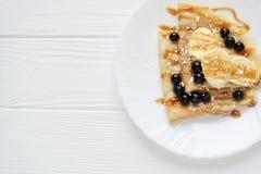 Crêpes avec les baies et la banane sur un fond blanc Photographie stock libre de droits