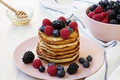 Crêpes avec les baies et le miel d'un plat rose au-dessus du fond en bois blanc, angle faible photo stock