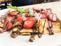 Crêpes avec les fraises et le chocolat fondu Plié, fermez-vous  image stock
