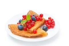 Crêpes avec les groseilles rouges et les myrtilles d'un plat d'isolement Photos stock