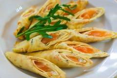 Crêpes avec les poissons rouges d'un plat Crêpes saumonées sur une table dans un restaurant photographie stock libre de droits