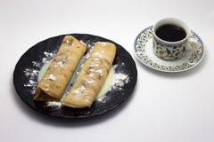 Crêpes chaudes délicieuses d'un plat noir avec une tasse de café d'isolement sur le fond blanc Images libres de droits