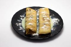 Crêpes chaudes délicieuses d'un plat noir d'isolement sur un fond blanc Image libre de droits