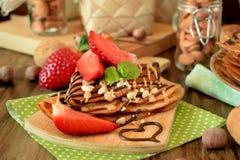 Crêpes décorées des écrous, du chocolat, des fraises fraîches et de la menthe Photos libres de droits