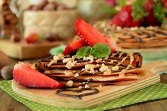 Crêpes décorées des écrous, du chocolat, des fraises fraîches et de la menthe Photos stock