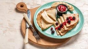 Crêpes délicieuses en gros plan, avec des myrtilles, des fraises et le sirop d'érable sur un fond clair Pile de crêpe Vue supérie images stock