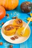 Crêpes d'or parfumées de potiron avec du miel et des noix sur un fond en bois bleu Photo stock