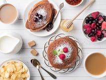 Crêpes de chocolat de petit déjeuner avec des baies, une tasse de café avec de la crème, le miel et des céréales Vue supérieure Image stock