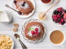 Crêpes de chocolat de petit déjeuner avec des baies, une tasse de café avec de la crème, le miel et des céréales Vue supérieure Images stock