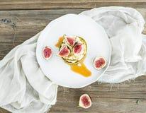 Crêpes de moelle /courgette avec les figues, le miel et le fromage de chèvre frais sur un petit morceau photographie stock