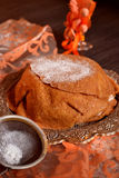 Crêpes de tarte avec du sucre en poudre sur un fond noir avec le tissu orange Photographie stock libre de droits
