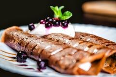 Crêpes de tiramisu avec de la crème et des baies, bonbon, chocolat de arrosage Photographie stock