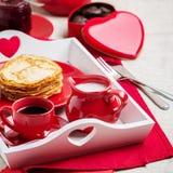 Crêpes et café de petit déjeuner avec du lait sur un plateau pour Valentine Photos libres de droits
